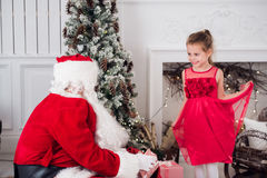 Santa Claus and children opening presents at fireplace. Kids father in costume wearing beard open Christmas gifts. Little girl helping with present sack Stock Photos