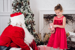 Santa Claus and children opening presents at fireplace. Kids father in costume wearing beard open Christmas gifts Royalty Free Stock Photography