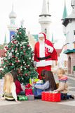 Santa Claus With Children Opening Presents vicino Immagini Stock Libere da Diritti