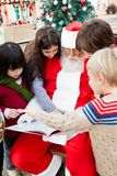 Santa Claus With Children Pointing At Book. Against Christmas tree in courtyard Stock Image