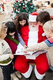 Santa Claus With Children Pointing At Book. In courtyard Stock Photography
