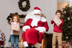 Santa claus and children with presents. Santa claus in rolling chair and children with christmas presents looking away at home Royalty Free Stock Images