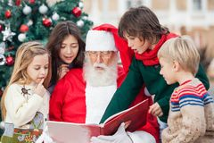 Santa Claus And Children Reading Book. Against Christmas tree Royalty Free Stock Images