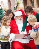 Santa Claus And Children Reading Book. In courtyard Royalty Free Stock Photography