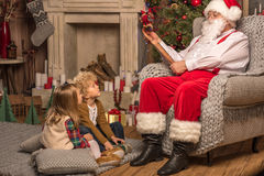 Santa Claus with children reading wishlist. Santa Claus reading wishlist and children looking at him Stock Photos