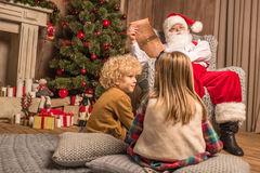 Santa Claus with children reading wishlist. Santa Claus reading wishlist while children sitting on carpet Stock Photos