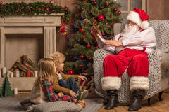 Santa Claus with children reading wishlist. Santa Claus reading wishlist while children sitting on carpet Royalty Free Stock Photo
