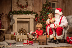 Santa Claus and children sitting near fireplace. Santa Claus and children sitting with gift boxes by fireplace Royalty Free Stock Photo
