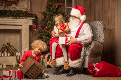 Santa Claus with children sitting near fireplace. And looking at gift boxes Stock Images