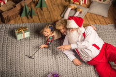 Santa Claus with children taking selfie. Santa Claus with children having fun and taking selfie on carpet Stock Image