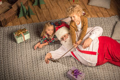 Santa Claus with children taking selfie. Santa Claus with children lying on carpet and taking selfie Stock Photos