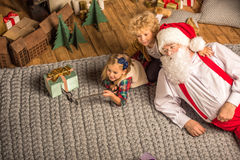 Santa Claus with children talking selfie. On grey carpet Royalty Free Stock Photo