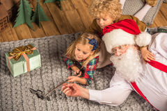 Santa Claus with children talking selfie. On grey carpet Stock Image