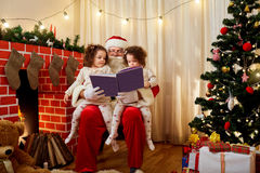 Santa Claus with children twin girls on his lap chiteyut book at. Christmas, New Year in the room by the fireplace and Christmas tree. The concept of Merry Royalty Free Stock Image