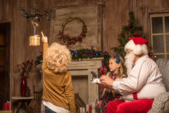Santa Claus with children using hexacopter drone. Santa Claus and children using hexacopter drone with flying gift box Stock Photography