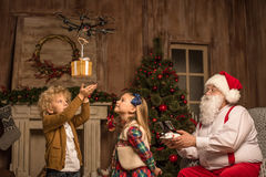 Santa Claus with children using hexacopter drone. Santa Claus using hexacopter drone while children looking at flying gift box Royalty Free Stock Photo