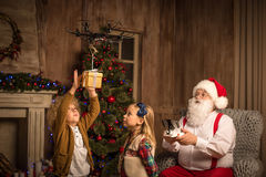 Santa Claus with children using hexacopter drone. Santa Claus using hexacopter drone while children looking at flying gift box Stock Photography