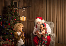 Santa Claus with children using hexacopter drone. In room Royalty Free Stock Images