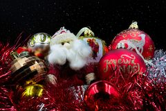 Santa Claus , Christmas balls red and gold. `Joyeux Noël`, `Happy Christmas`, Santa Claus , Red and gold Christmas balls on a background of starry sky Stock Photography