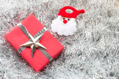 Santa claus, Christmas gift box and decoration. On silver fir twigs background Stock Photography