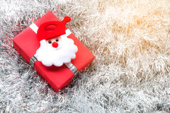 Santa claus, Christmas gift box and decoration on silver fir twigs. Background Stock Photos