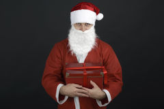 Santa Claus with Christmas Gift Box. Isolated on Black Background Stock Photo