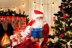 Santa Claus at Christmas with gifts bag opens the box next to th. E Christmas tree and fireplace in the room Stock Photos