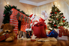Santa Claus at Christmas with gifts bag opens the box next to th. E Christmas tree and fireplace in the room Royalty Free Stock Photos