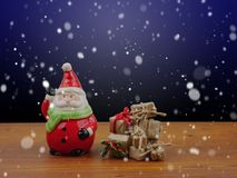 Santa Claus and Christmas gifts among falling snow at night  Christmas,festival,holiday concept Royalty Free Stock Images
