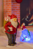 Santa Claus with Christmas gifts. Santa Claus with Christmas gift bag in front of a fireplace Stock Image