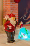 Santa Claus with Christmas gifts. Santa Claus with Christmas gift bag in front of a fireplace Royalty Free Stock Photo