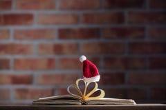 Santa Claus Christmas hatt och gamla böcker Royaltyfria Bilder