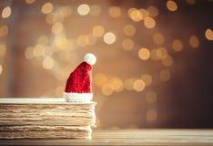 Santa Claus Christmas hatt och gamla böcker Arkivbild