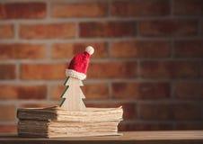 Santa Claus Christmas hatt och träd med gamla böcker Royaltyfri Foto