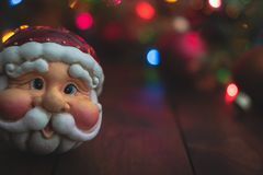Santa Claus Christmas ornament in front of a decorative background with room for messaging. Santa Claus Christmas ornament in front of a decorative brown royalty free stock image