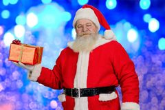 Santa Claus with Christmas present. Portrait of old Santa Claus holding red gift box on blue shimmering background. New Year and Christmas holiday concept Stock Photos