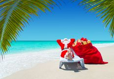 Santa Claus with Christmas sack full of gifts relax on sunlounge. R barefooted at perfect sandy ocean beach under palm tree leaves. Happy New Year travel royalty free stock photo