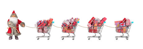 Santa Claus christmas shopping. Santa Claus out for shopping, dragging four filled shopping carts with christmas gifts Royalty Free Stock Photos