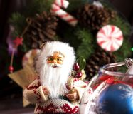 Santa Claus and Christmas tree toys in a round glass vase. Santa Claus and the Christmas tree toys in a round glass vase royalty free stock photo