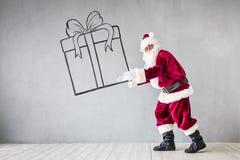 Santa Claus Christmas Xmas Holiday Concept. Santa Claus holding gift box. Christmas Xmas holiday concept stock image