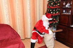 Santa Claus and Christmass tree during Xmas with happy girl Stock Photography
