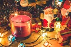 Santa Claus chwyta dzwon świeczka i boże narodzenia, ornament dekorujemy Wesoło boże narodzenia i szczęśliwego nowego roku Fotografia Stock