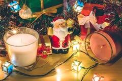 Santa Claus chwyta dzwon, biel i fiołków boże narodzenia świeczki, ornament dekorujemy Wesoło boże narodzenia i szczęśliwego nowe Zdjęcie Royalty Free