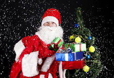 Santa Claus. Classic Santa holding a lot of Christmas gifts Stock Image