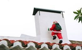 Santa Claus climbing the chimney. Santa Claus climbing the white chimney Royalty Free Stock Photos