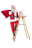 Santa claus climbing a ladder Royalty Free Stock Photos