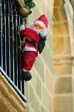 Santa Claus climbing up house Royalty Free Stock Photo