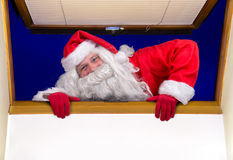 Santa Claus climbs at open window Stock Photo
