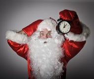 Santa Claus and a clock Royalty Free Stock Image