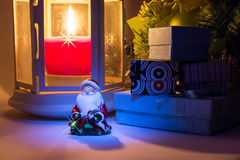 Santa Claus close up with lantern with burning candle and Christmas tree with Santa Claus and gift boxes with shadows Stock Photography